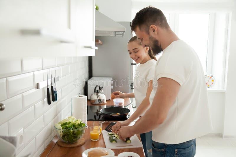 Lyckliga par som tillsammans förbereder frukosten i kök i morgon arkivbilder