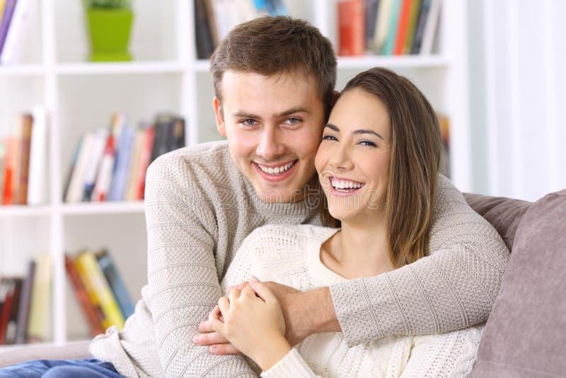 Lyckliga par som tillsammans hemma poserar på en soffa arkivfoto