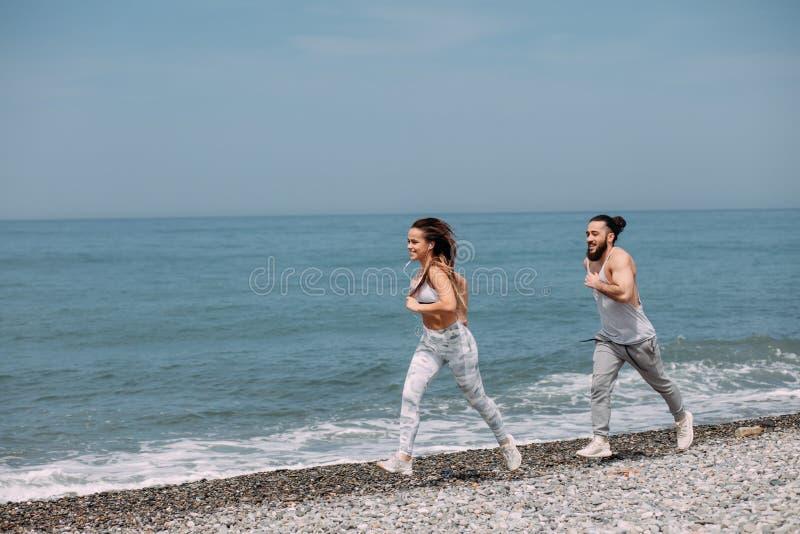 Lyckliga par som tillsammans kör bredvid vattnet på stranden royaltyfria foton