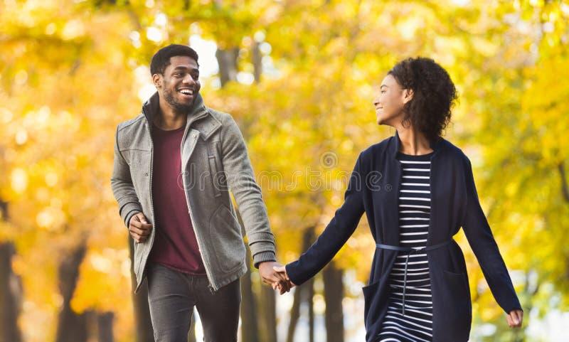 Lyckliga par som tillsammans kör i höst, parkerar royaltyfri bild