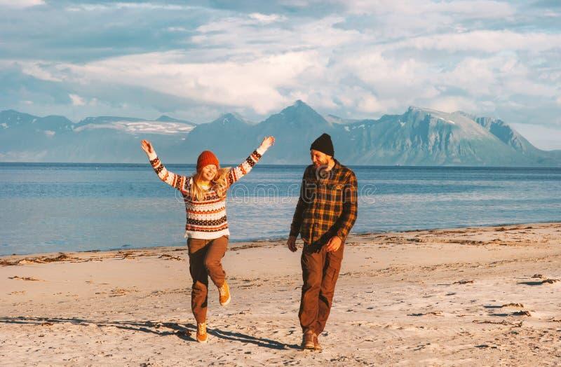 Lyckliga par som tillsammans reser glat, går på stranden arkivbild