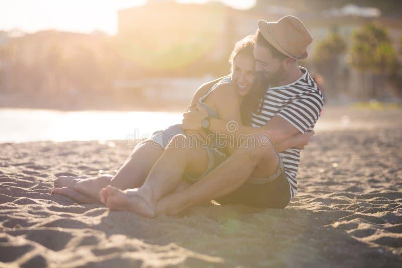 Lyckliga par som tillsammans sitter på stranden som kramar sig arkivbild