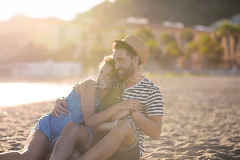Lyckliga par som tillsammans sitter på strandkel arkivfoton