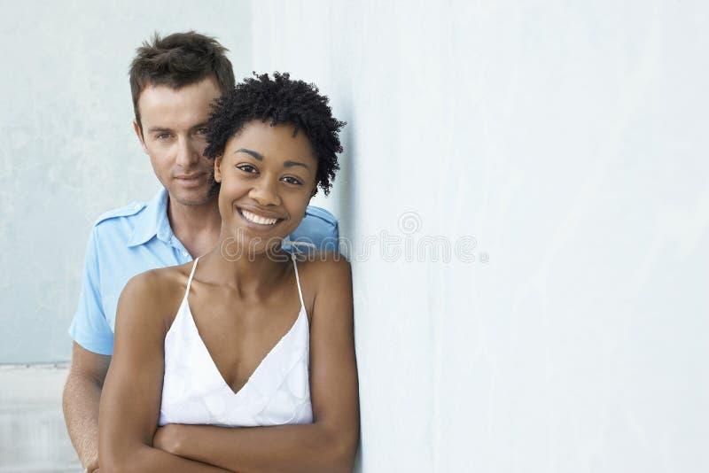 Lyckliga par som tillsammans står mot väggen royaltyfria bilder