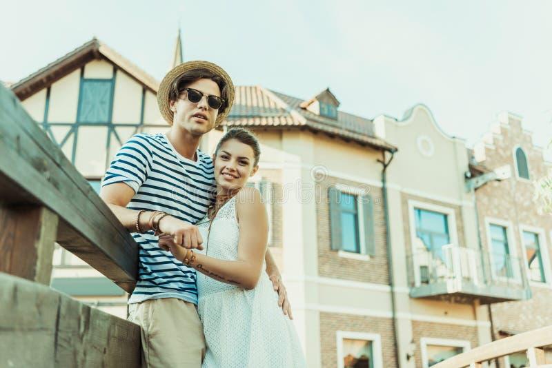 Lyckliga par som tillsammans står på bron, gamla byggnader på bakgrund royaltyfri foto