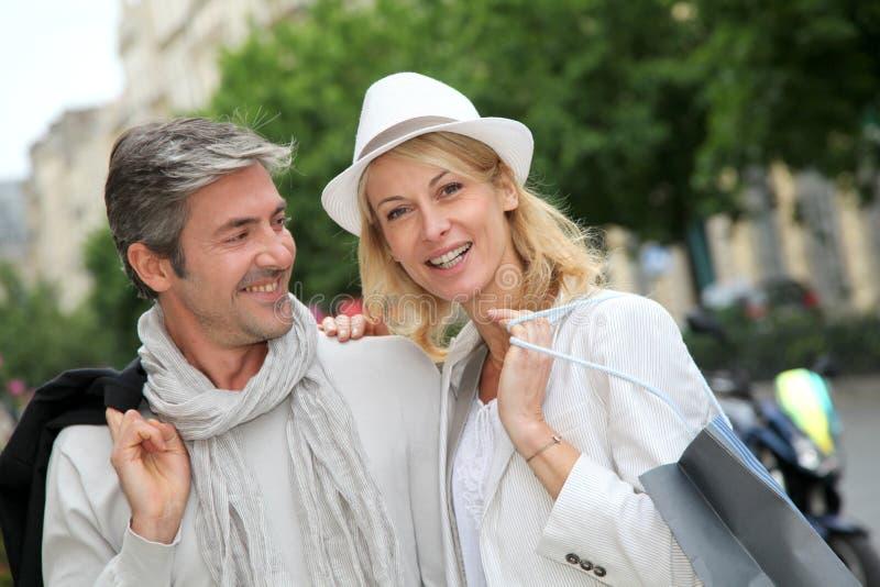 Lyckliga par som tycker om att shoppa i staden fotografering för bildbyråer