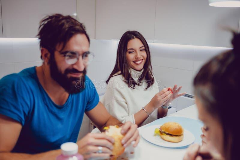 Lyckliga par som tycker om matställen med vänner royaltyfria bilder