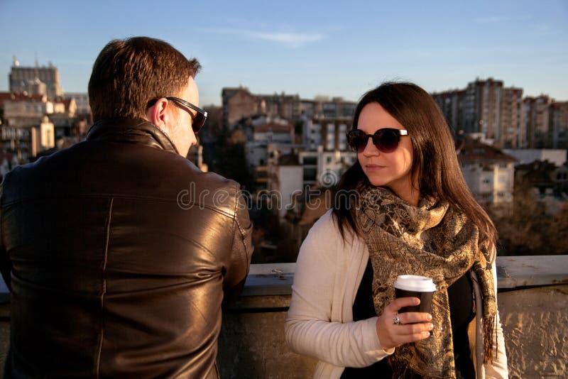 Lyckliga par som tycker om solen på taket i staden arkivfoto