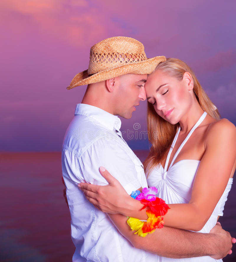 Lyckliga par som tycker om solnedgång på stranden royaltyfria bilder