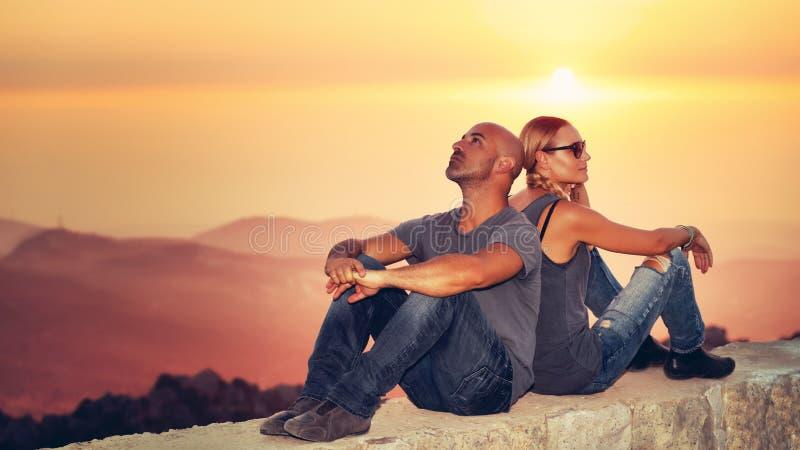 Lyckliga par som tycker om solnedgångsikt royaltyfri fotografi