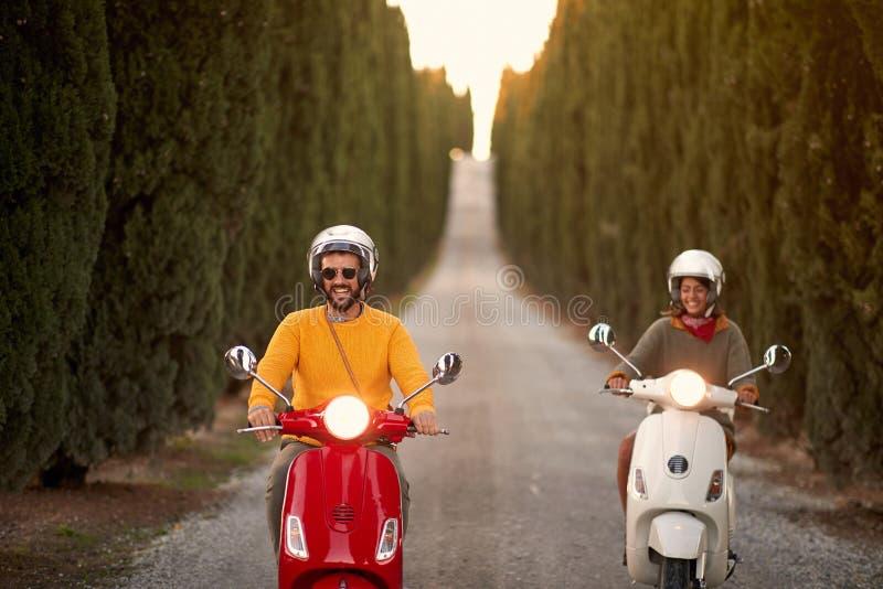 Lyckliga par som utomhus rider en sparkcykel arkivfoto