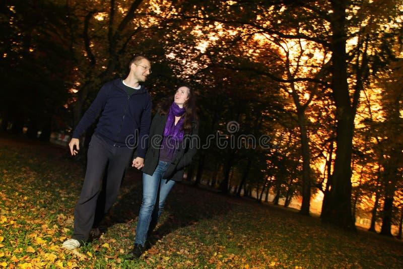 Lyckliga par som wallking till och med hösten, parkerar royaltyfri foto