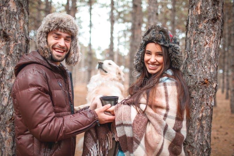 Lyckliga par spenderar tid i höstskogen med en hund royaltyfria foton