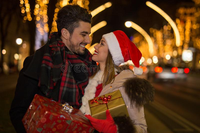 Lyckliga par utanför för jul som ler på de arkivbilder