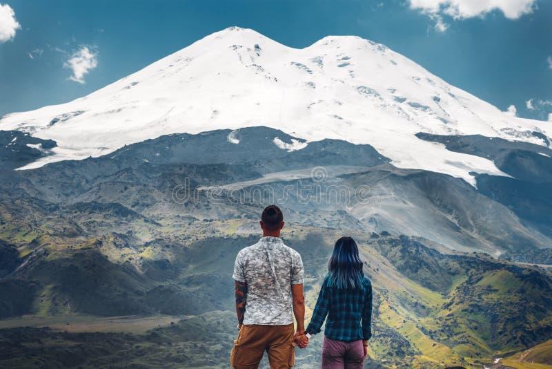 Lyckliga parinnehavhänder och tycka om sikten av Mount Elbrus royaltyfria foton