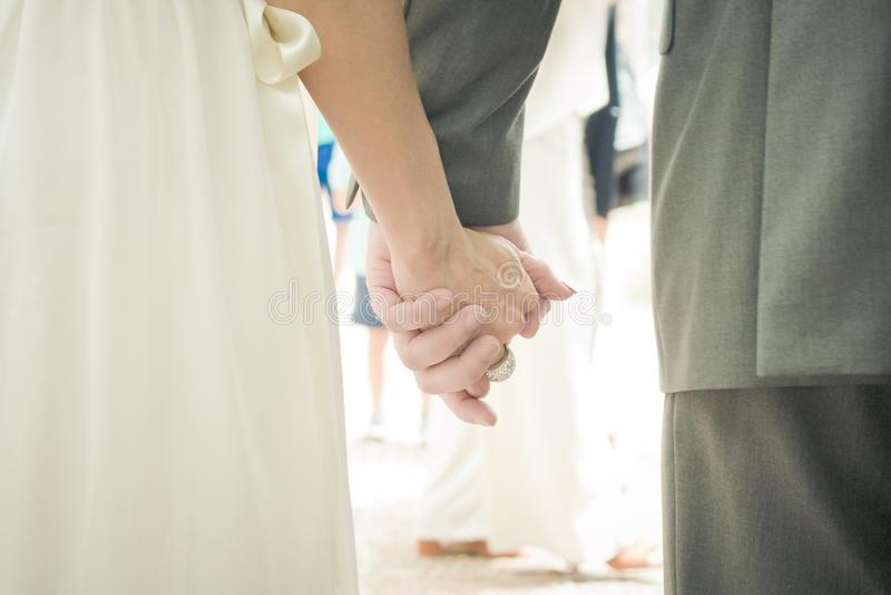Lyckliga parinnehavhänder på deras bröllopdag arkivbild