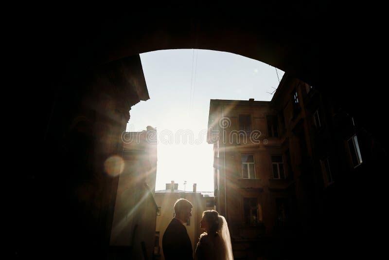 Lyckliga parinnehavhänder på solnedgång, nygift personbrud och brudgum p royaltyfri fotografi