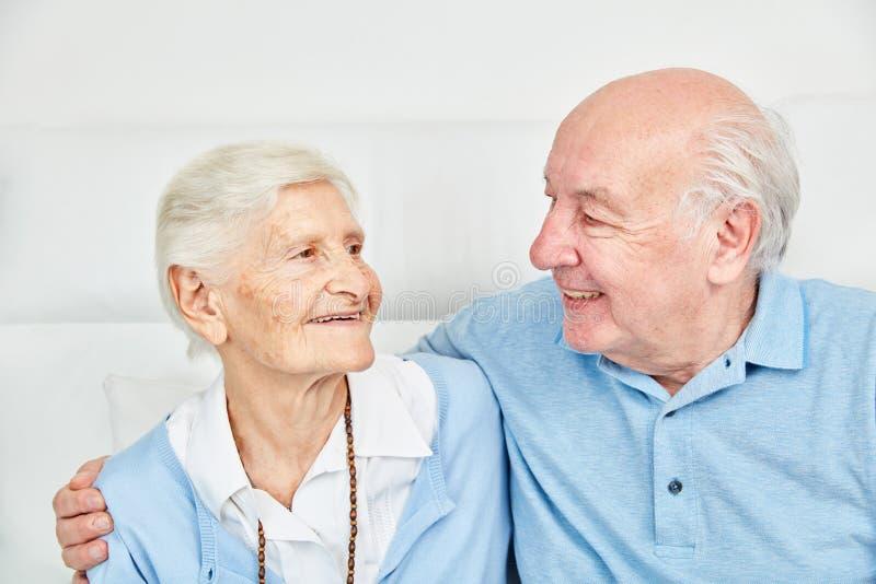Lyckliga parpensionärer som hemma kramar sig arkivfoton
