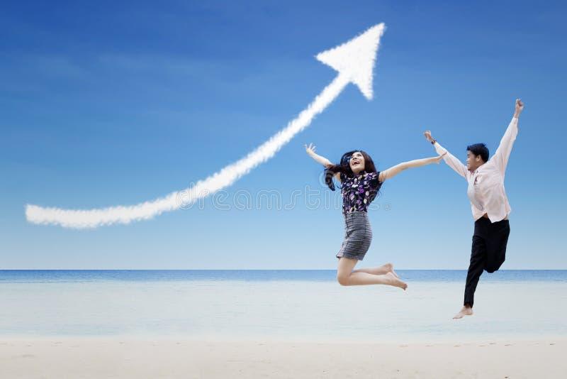 Lyckliga partners hoppar under molnet för förhöjningpiltecknet på stranden arkivfoton