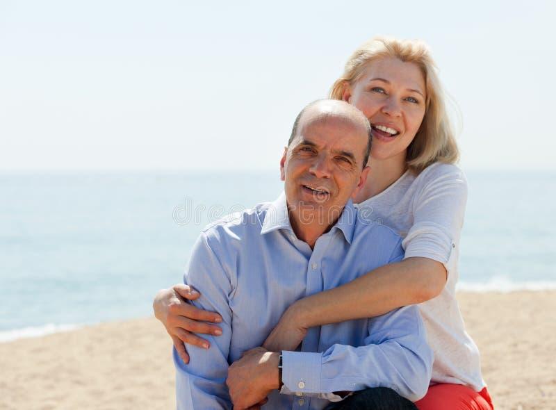 Lyckliga parturister på stranden på att le för semester arkivbilder