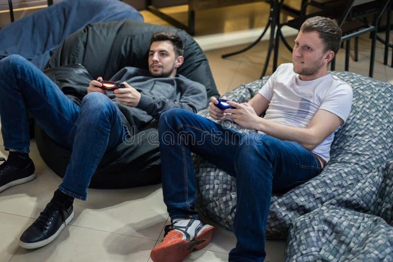 Lyckliga parvänner som spelar videospel med styrspaksammanträde på stol för bönapåse royaltyfri foto