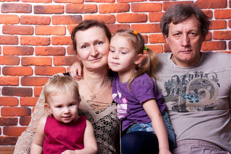 lyckliga pensionärer för parbarnbarn royaltyfri foto