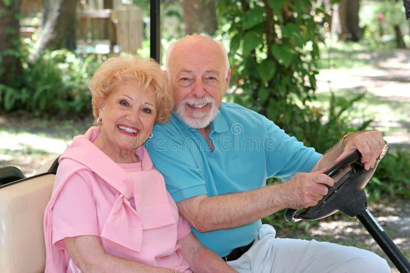 lyckliga pensionärer för vagnsgolf arkivbilder