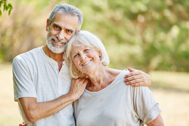 Lyckliga pensionärer som kramar och ler royaltyfri fotografi