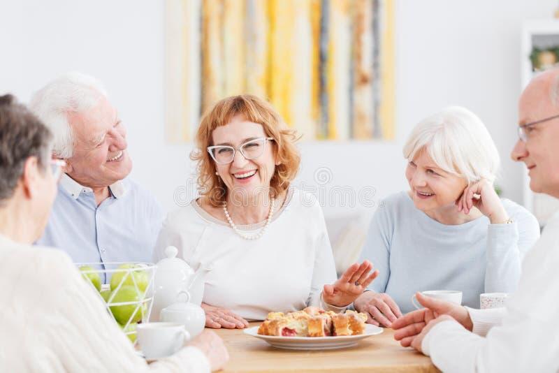 Lyckliga pensionärer som pratar på kafét arkivbilder