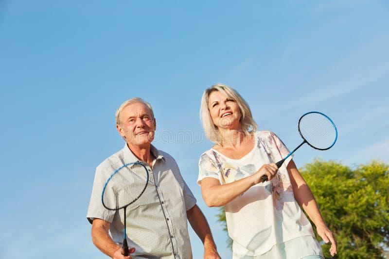 Lyckliga pensionärer som spelar badminton royaltyfria foton