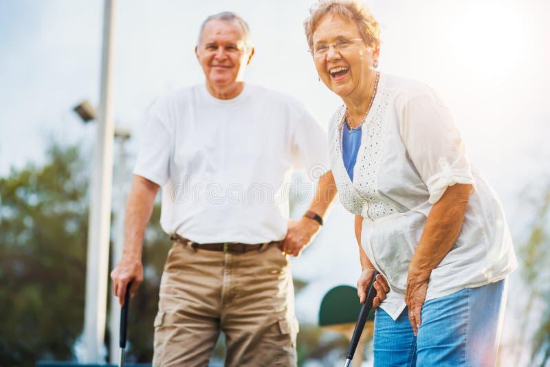 Lyckliga pensionärer som spelar mini- golf royaltyfria foton
