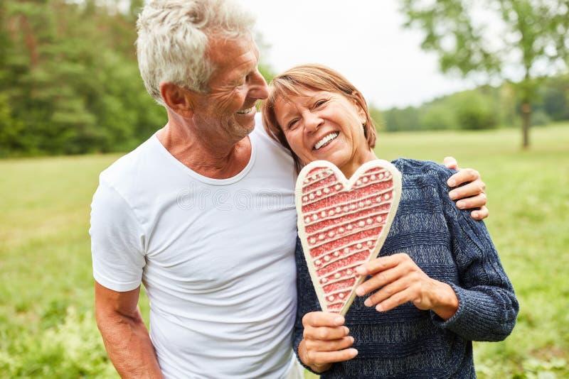 Lyckliga pensionärpar med pepparkakahjärta arkivfoton