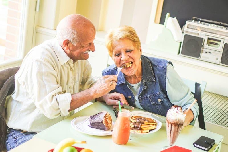 Lyckliga pension?rpar som ?ter pannkakor i en st?ngrestaurang - pensionerat folk som har gyckel som tillsammans tycker om lunch arkivbild