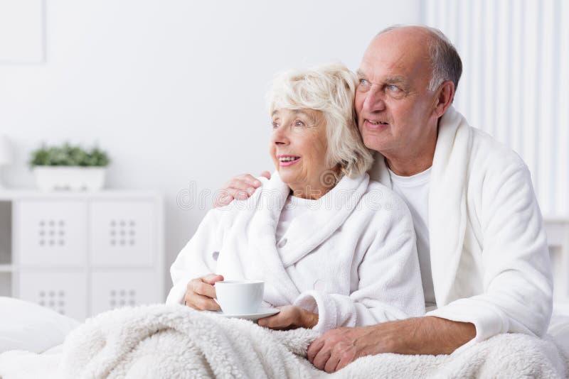 Lyckliga pensionerade par i säng arkivbilder