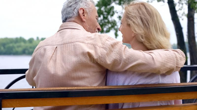 Lyckliga pensionerade par som kopplar av på, parkerar bänken som utanför tycker om helg, förälskelse royaltyfria bilder