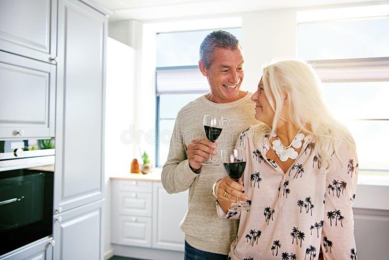 Lyckliga pensionerade par som tycker om ett exponeringsglas av vin royaltyfri foto