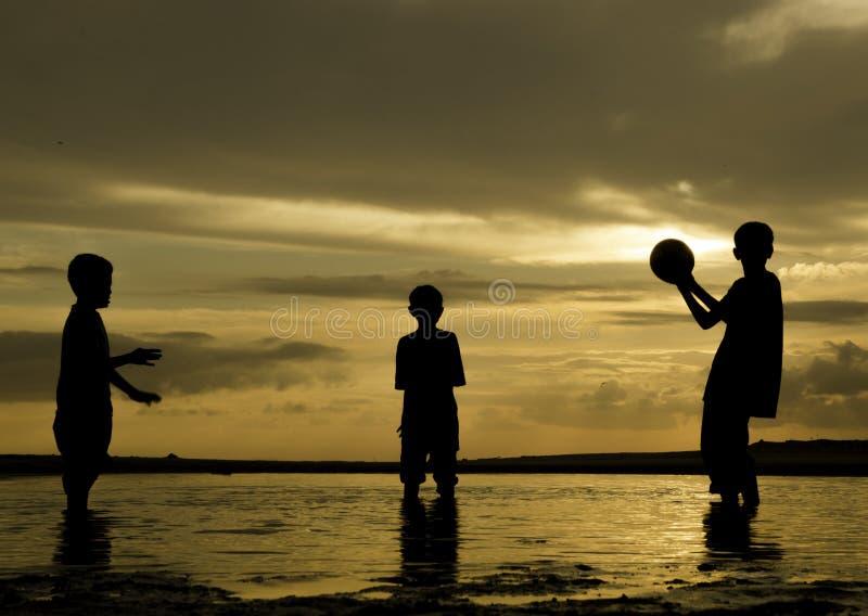 Lyckliga pojkar för konturbild som spelar strandfotboll på gryningtid med härlig soluppgångbakgrund royaltyfri fotografi