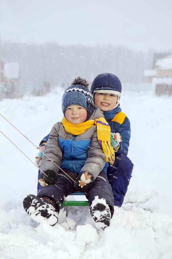 Lyckliga pojkar på släden royaltyfri foto