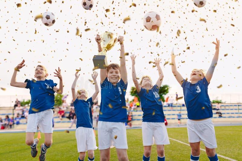 Lyckliga pojkar som firar fotbollmästerskap Ungdomfotboll som segrar Team Jumping och den stigande guld- koppen på troféceremoni royaltyfria foton