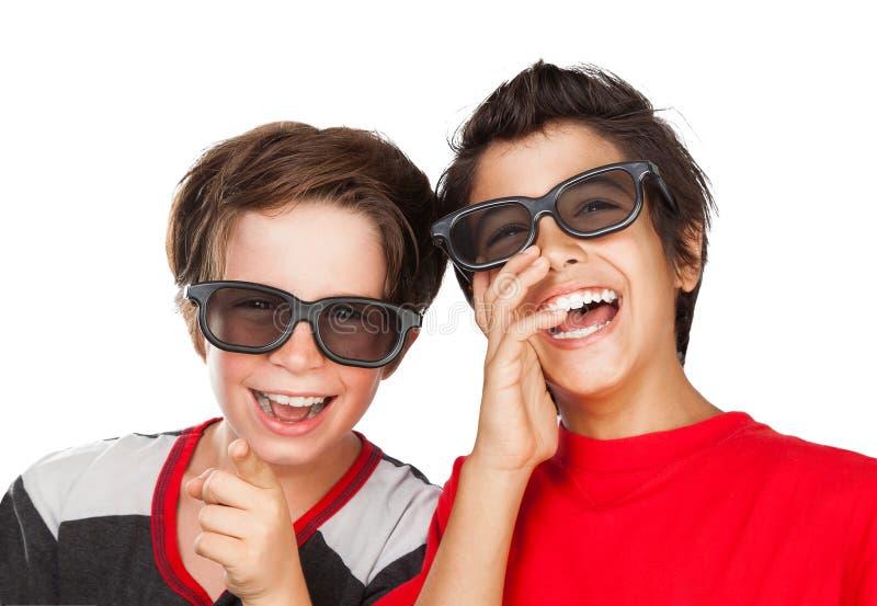 Lyckliga pojkar som håller ögonen på film royaltyfri fotografi