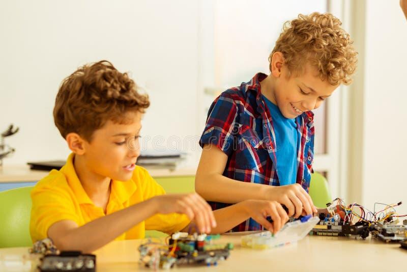 Lyckliga positiva pojkar som tillsammans konstruerar olik leksaker arkivfoto