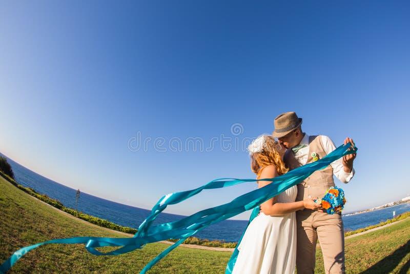 Lyckliga precis gifta unga brölloppar som firar att kyssa och, har gyckel på den härliga stranden royaltyfria bilder