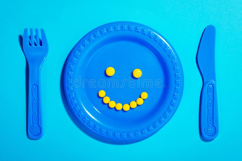 Lyckliga preventivpillerar på barnplattan arkivbilder
