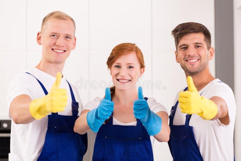 Lyckliga rengöringsmedel på arbete royaltyfri bild