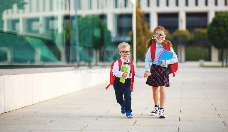 Lyckliga roliga barn skolflicka och skolpojkestudentgrundskola arkivbilder