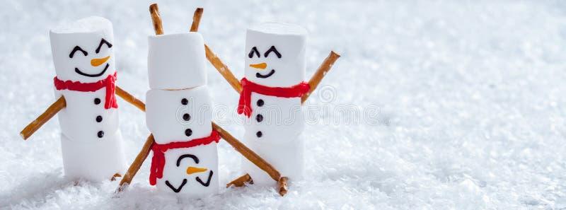 Lyckliga roliga marshmallowsnowmans på snö royaltyfria foton