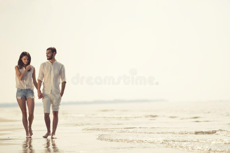 Lyckliga roliga strandsemestrar kopplar ihop att gå tillsammans att skratta ha gyckel på loppdestination royaltyfria bilder