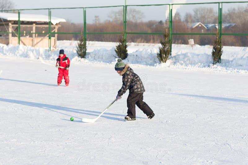 Lyckliga roliga ungar som spelar hockey på isbanan arkivbild