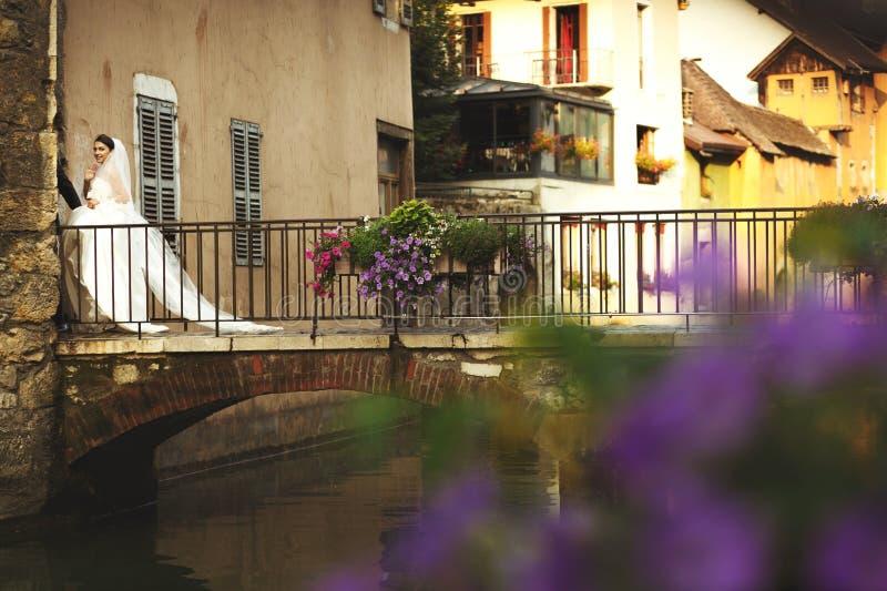 Lyckliga romantiska gift parinnehavhänder på den gamla bron i ann royaltyfria bilder