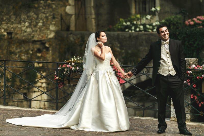Lyckliga romantiska gift parinnehavhänder på stenbron med fotografering för bildbyråer